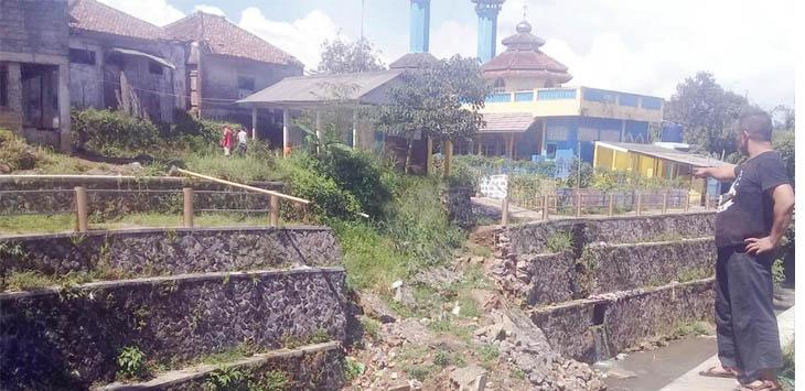 WASPADA: Salah seorang warga Kampung Cijangkar menunjukan lokasi longsor