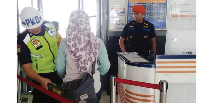 Salah seorang petugas Stasiun KA Sukabumi memeriksa penumpang
