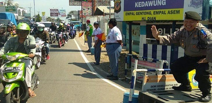 Kepala Polsek Kedawung, AKP Tutu Mulyana menghibur pemudik dengan joged di Pos Pam Kedawung, Jalan Pantura Cirebon, Rabu (13/6)./Foto: via Jawapos