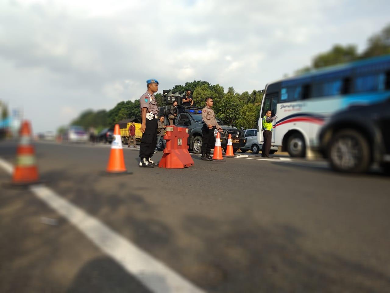 Petugas kepolisian sedang mengatur kendaraan roda empat di Rest Area 207 A, Kecamatan Mundu, Kabupaten Cirebon. Foto: Alwi