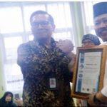 Kepala Disdukcapil Kabupaten Sukabumi, Sofyan Efendy saat menerima sertifikat ISO 9001:2015 dari LSSM - ICSM.