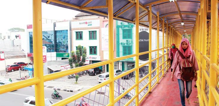 Pejalan kaki saat melintas di salah satu Jembatan Penyeberangan Orang (JPO) di Jalan Margonda Raya, kemarin. Ahmad Fachry/Radar Depok