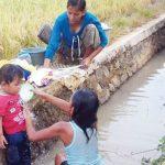 KOTOR: Ibu dan anak gunakan air keruh sungai Muara Citaraje untuk mencuci dan mandi. Gani/Radar Karawang