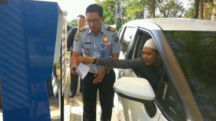 Petugas Imigrasi sedang membantu pemohon paspor mengambil paspornya yang sudah jadi dalam pelayanan Lantatur. Foto: Alwi