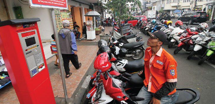 Juru Parkir sedang memerhatikan mesin parkir otomatis di salah satu jalan kota Bandung.