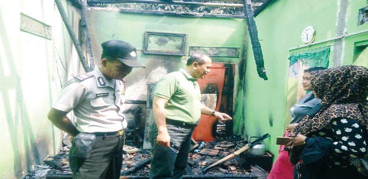 PANTAU LOKASI: Petugas kepolisian dan pemadam kebakaran saat memeriksa rumah kontrakan yang hangus terbakar di Desa Rawasari, Kecamatan Plered. Gani/Radar Karawang