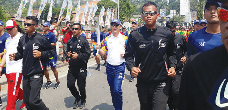 KELILING: Sejumlah pejabat dan atlet bergiliran membawa obor Asian Games sambil berlari. Puncaknya, obor ini akan singgah di Taman Air Mancur Sri Baduga. Gani/Radar Karawang