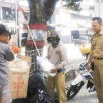 BERSEDEKAH: Lurah Muka, Sopyan (tengah) saat mengumpulkan sampah yang sudah di pilah dari warga.