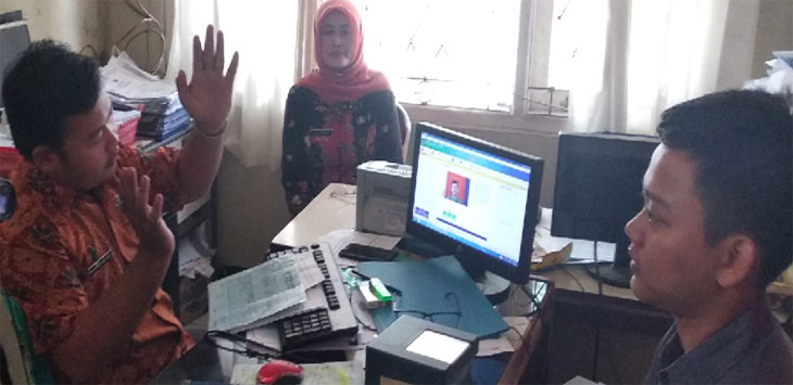 RUSAK: Petugas Rekam KTP elektronik Telukjambe Timur Amung (kiri) menjelaskan kerusakan sidik jari. YOFA FAISAL NILAN / RADAR KARAWANG