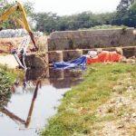 Beco sedang mengeruk sampah di Sungai Cikaranggelam. Banyaknya sampah di gorong-gorong sipon menjadi biang kerok banjir tahunan. ASEP SOPIAN/RADAR KARAWANG