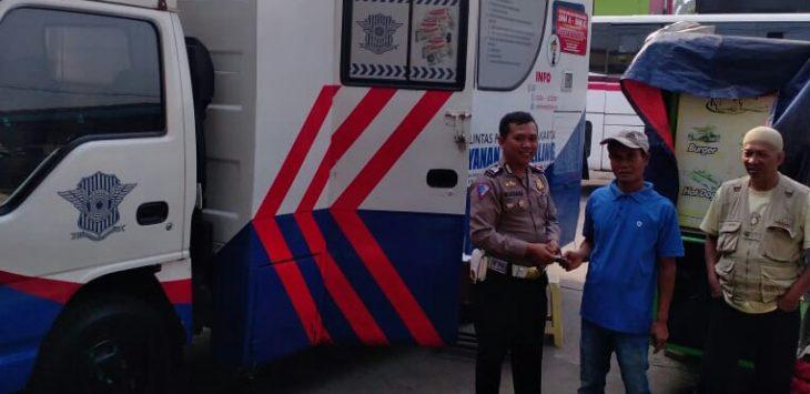 Salah satu anggota polisi saat berfoto bersama dengan masyarakat yang memperpanjang SIM di mobil sim keliling