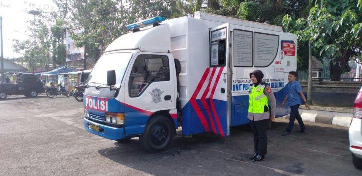 Salah satu anggota kepolisian saat bersiap melayani perpanjangan SIM di mobil sim keliling