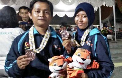 TUNJUKAN MEDALI : Pasangan suami istri atlet Purwakarta menunjukan medali perunggu yang diraih di Porda Jabar XIII. Gani/Radar Karawang