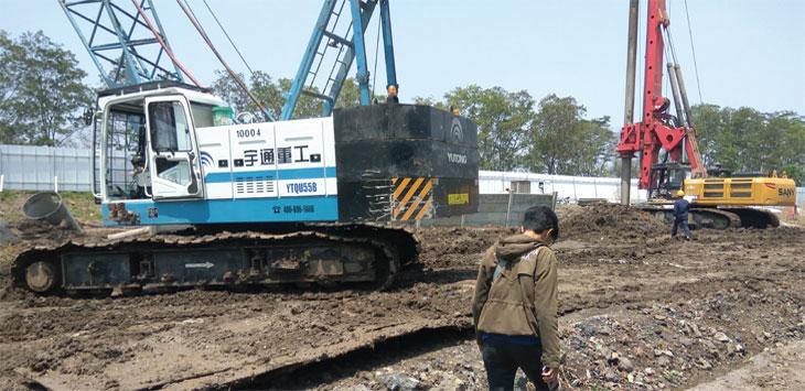 KCIC : Warga melintasi alat besar yang digunakan pengembang PT. Kereta Cepat Indonesia Cina (KCIC) di Cimahi. WIHNU PRADANA/RADAR BANDUNG