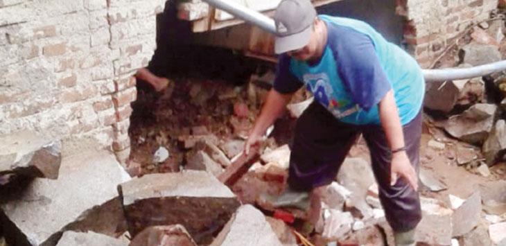 Warga saat membersihkan bekas longsor di rumah Osid dan Yayah.