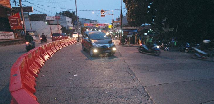 AKAN DIPERMANEN : Pengendara melintas di putaran arah pertigaan Jalan Raya Kartini, Minggu (9/12). Dinas Perhubungan (Dishub) Kota Depok akan mempermanenkan putaran balik yang ditutup oleh pembatas jalan di tiga titik. Ahmad Fachry/Radar Depok