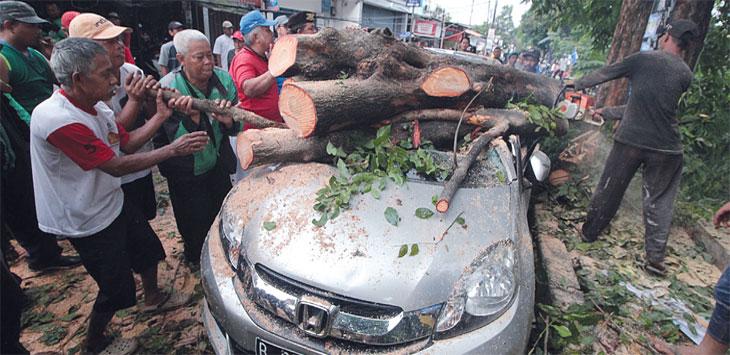 EVAKUASI POHON TUMBANG: Warga bergotong-royongmengevakuasi pohon tumbang yang menimpa salah satu mobil di kawasan Jalan Raya Tanah Baru, Kelurahan Tanah Baru, Kecamatan Beji, Minggu (13/1/19). Ahmad FAchry/Radar Depok