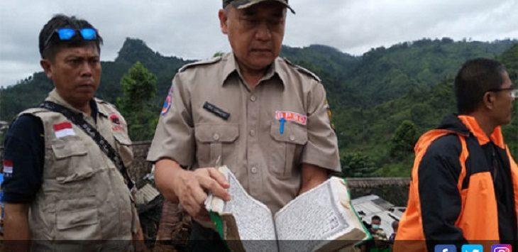 Sekda Kabupaten-Sukabumi Iyos Somantri saat memeriksa Alquran yang ditemukan di tengah-tengah area longsor./ Foto-rendiradar-sukabumi (jpnn)