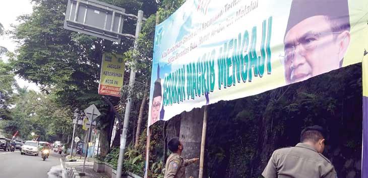 PENGECEKAN: Petugas Satpol PP Kota Sukabumi saat melakukan pengecekan spanduk magrib mengaji yang terpasang di perempatan lampu merah degung yang dirobek orang tidak bertanggungjawab.