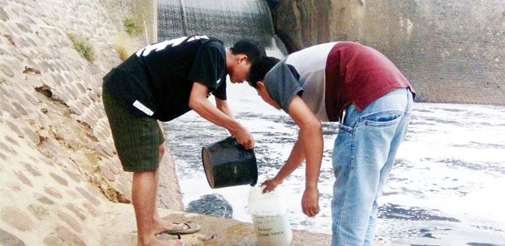 AMBIL SAMPEL: Pegiat lingkungan mengambil sampel air Bendung Barugbug untuk diteliti. Air bendung ini tidak pernah jernih, selalu tercemar. Berwarna hitam dan bau. ASEP SOPIAN/RADAR KARAWANG