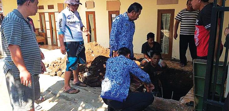Koko Komarudin saat meninjau lokasi saluran air pembuangan yang tersumbat. TOHA HAMDANI/RADAR SUMEDANG