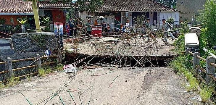 Warga menutup jalur jembatan desa dengan bambu.