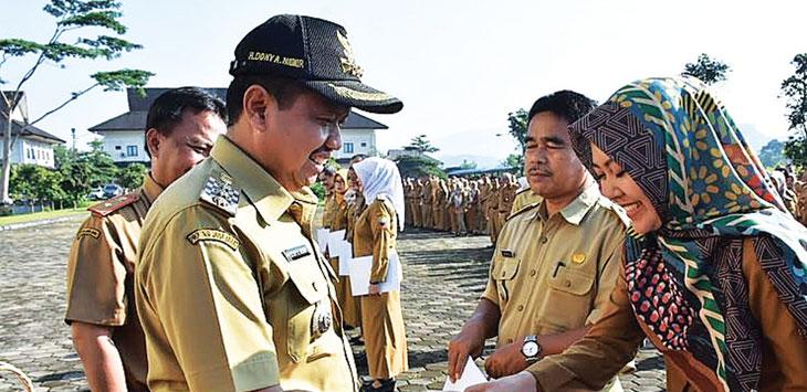 Bupati Sumedang, H. Dony Ahmad Munir menyerahkan bingkisan kepada Karyawan Humas dan Protokol Setda Sumedang, Riestina Martiani di lapangan IPP Setda. Radar Sumedang