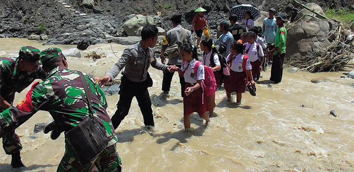 Siswa SD dibantu aparat, harus menyebrang sungai akibat jembatan gantung Cisaar Desa Desa Cipicung Kecamatan Jatigede, terputus. Radar Sumedang