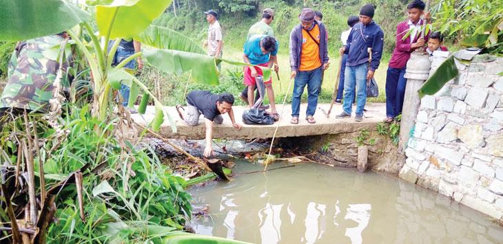 Sejumlah pemuda pada saat membersihkan sampah di aliran sungai.