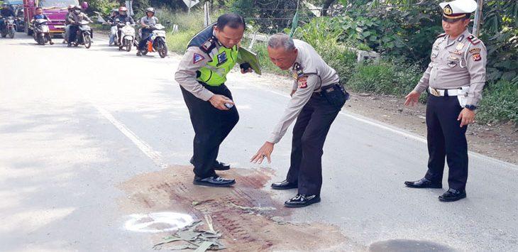 Anggota Polres Purwakarta menutup bekas kecelakaan dengan menggunakan tanah. Radar Karawang