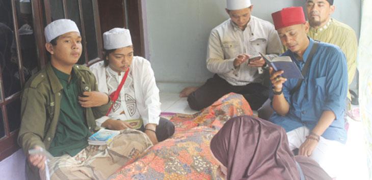 Keluarga dan kerabat Farhan Safero saat mengaji didepan jenazah dirumah duka RT2/7, Kelurahan Grogol, Kecamatan Limo, rabu (22/5/19).