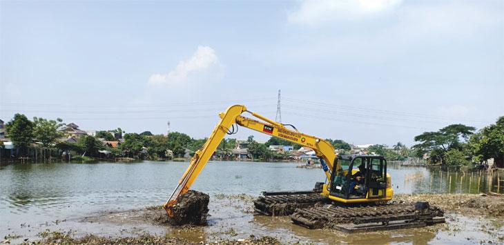 Alat berat Amfibi berukuran PC 70 sedang mengeruk tanah dan lumpur di Situ Citayam yang sedang dalam proses normalisasi oleh Dinas PUPR Kota Depok, Selasa (7/5/19). Radar Depok