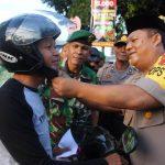 Kapolres Indramayu pakaikan helm kepada pengendara sepeda motor. Yanto/pojokjabar