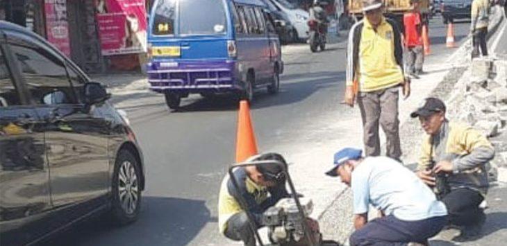 Petugas Dinas PUPR Kota Depok dan Dishub Depok membongkar separator di Jalan Nusantara Raya, kamis (24/5/19). Radar Depok