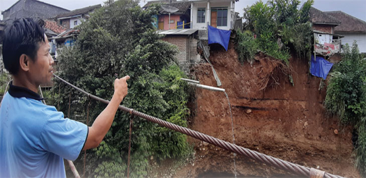 Karna, warga Kampung Warung Kalapa, RT 01/01, Kelurahan Lembursitu, Kecamatan Lembursitu saat menunjukan lokasi longsor. Radar Sukabumi