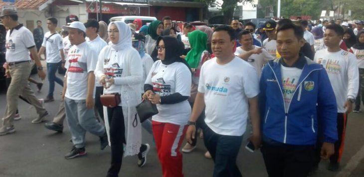 Ketua KNPI Purwakarta Asep Supriatna (kaos bertiliskan pemuda) saat mendampingi Bupati Anne Ratna Mustika, saat jalan santai dalam peringatan HUT Bhayangkara ke 73