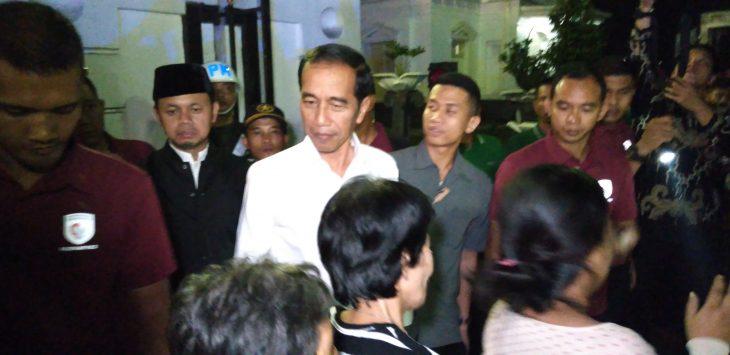 Presiden Joko Widodo bagikan paket sembako kepada warga Bogor di depan pintu Istana Bogor di malam takbiran