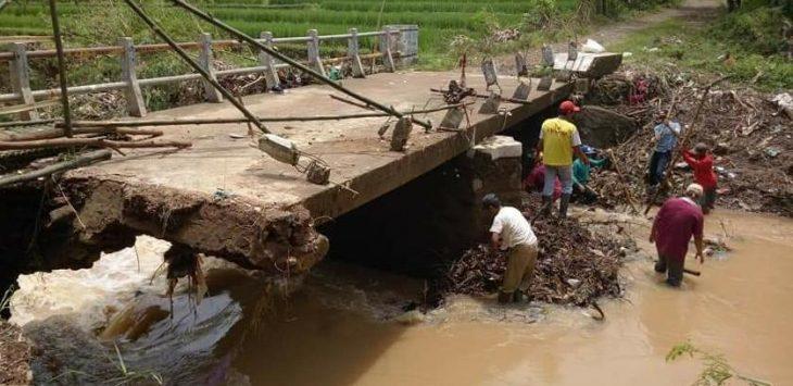 Jembatan Penghubung satu-satunya rusak 3 tahun lalu, warga berswadaya menopang dengan kayu kelapa di aliran sungai Singaraja Desa Leuwidinding. Indra/pojokjabar