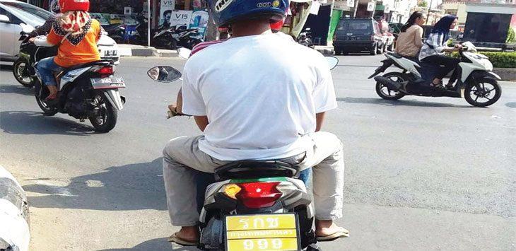 Pengendara sepeda motor menggunakan plat nomor khas Thailand terlihat santai melintas di Jalan Jenderal Sudirman Purwakarta. Anak muda ini tampak santai tanpa rasa takut ditindak polisi.