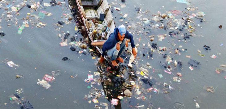 Seorang warga sedang mencari sampah botol plastik menggunakan perahu di aliran Sungai Citarum, Batujajar, Kabupaten Bandung Barat.