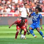 Hariono berebut bola dengan Riko Simanjuntak di babak pertama
