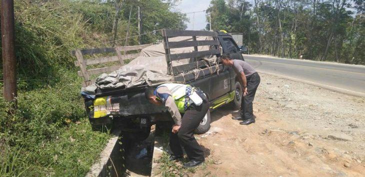 Dua anggota polisi memeriksa kolong mobil yang menabrak pengendara motor, memastikan tak ada korban jiwa lainnya.