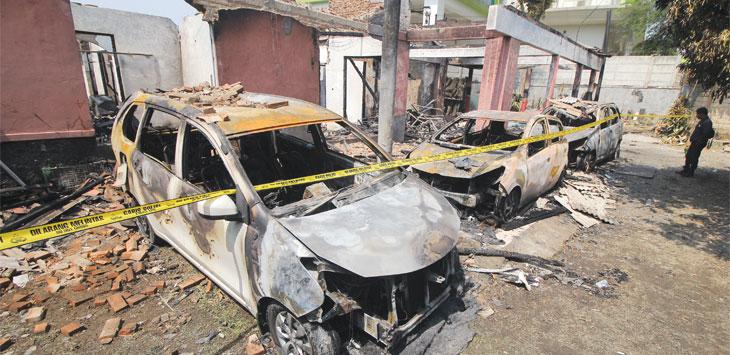 Warga melihat kondisi bangunan dan kendaraan roda empat yang hangus terbakar di Soundgraph Studio, Jalan Kartini Raya, Kecamatan Pancoranmas, Selasa (16/7/19). Radar Depok