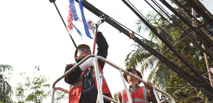 Walikota Depok Mohammad Idris sedang memotong kabel udara di Pintu Gerbang Balaikota Depok, jum'at (12/7/19).