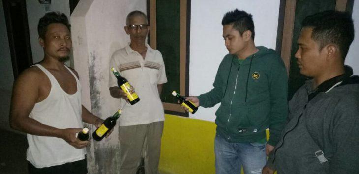 Anggota sat res narkoba dan masyarakat berikut rt setempat saat memperlihatkan miras pabrikan dan oplosan hasil menggerebeg di depan kontrakan JN
