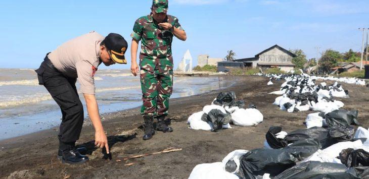 Aparat ketika melihat pantai yang tercemar kebocoran minyak di Laut Karawang (ega)
