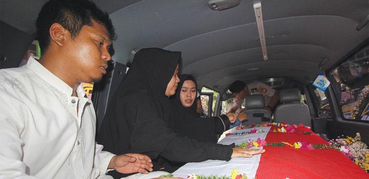 Anggota keluarga mengantarkan peti yang berisikan jenazah Bripka Rahmat Effendy (41) yang akan dibawa ke TPU Jonggol, Desa Singasari, Kecamatan Jonggol, Kabupaten Bogor Jumat (26/7/19).