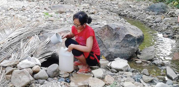 Seorang warga asal Kampung Tegaldatar, RT 19/5, Desa Neglasari, Kecamatan Lengkong , saat mengambil air ke jerigen di sungai Cikaso Cikaler, untuk kebutuhan sehari-hari seperti mencuci, mandi dan masak.