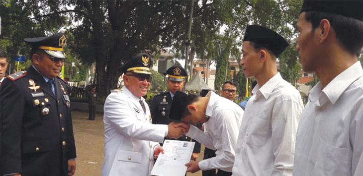 Walikota Depok Mohammad Idris menyerahkan surat keputusan remisi bebas secara simbolis kepada tiga Nara Pidana Rutan Kelas IIB Depok, pada Upacara HUT ke-74 Kemerdekaan RI, di Balaikota Depok, Sabtu (17/8/19). Radar Depok