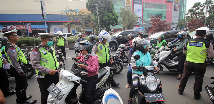 Petugas kepolisian Satlantas Polresta Depok saat melakukan pemeriksaan kelengkapan surat kendaraan pengendara di Jalan Margonda Raya. Radar Depok